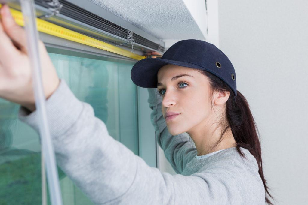 kobieta mierząca okno
